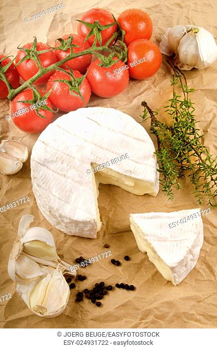 camembert with garlic, black pepper, wet tomato and thyme on brown kitchen paper