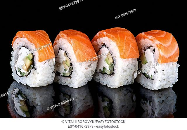 Sushi roll Philadelphia in row rotated. Black background with reflection