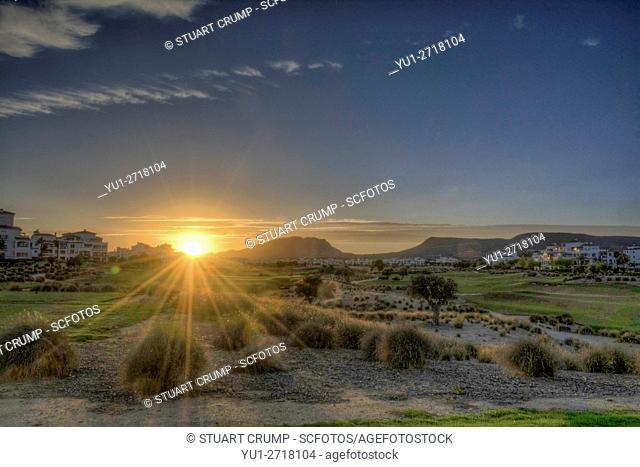 Sun setting behind the mountains at Hacienda Riquelme Golf Resort