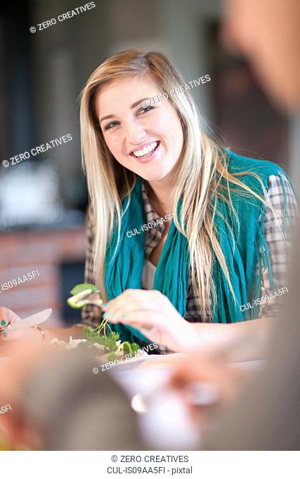 Young woman eating salad in kitchen