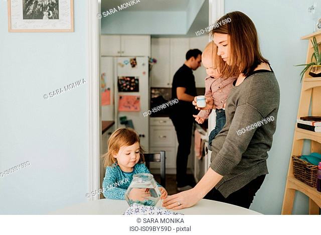 Female toddler at table with mother and baby brother
