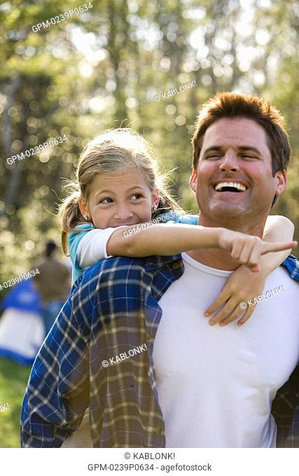 Father piggybacking daughter in park, smiling
