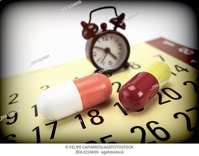 Pills on a calendar along with a clock, conceptual image