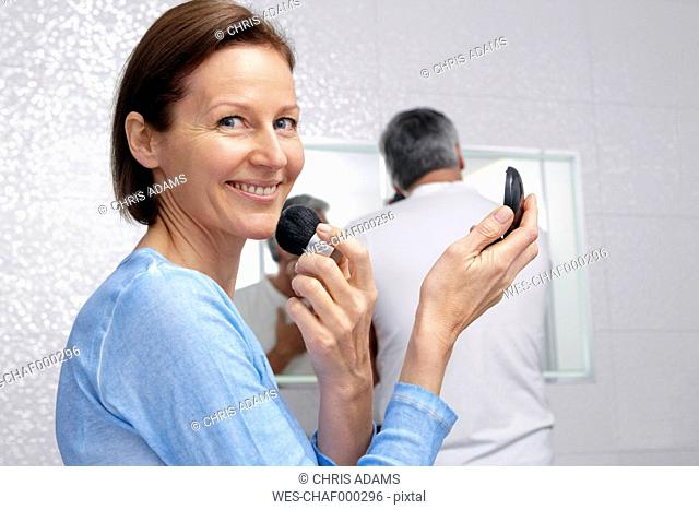 Smiling mature woman applying make up on face while her husband shaving in the background