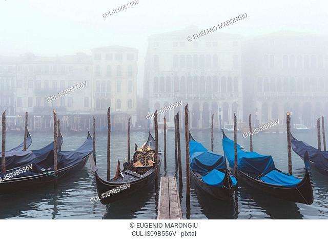 Rows of gondolas on misty canal, Venice, Italy