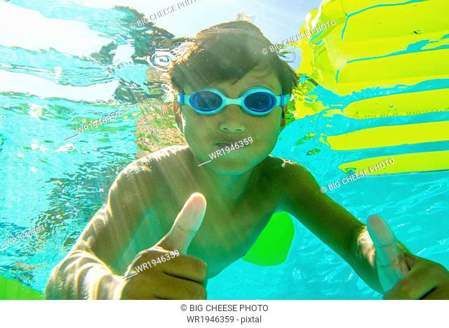 Underwater view of a boy swimming wearing goggles