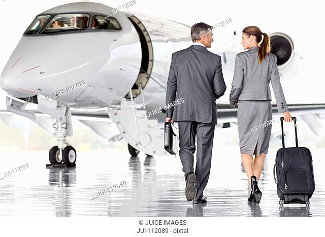 Businesswoman and Businessman walking toward private jet