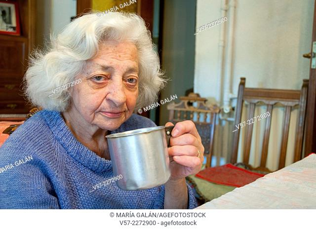 Old woman at home, drinking coffee and looking at the camera