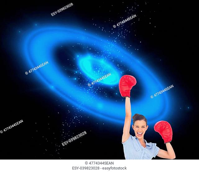 Composite image of businesswoman cheering wearing boxing gloves on galaxy background