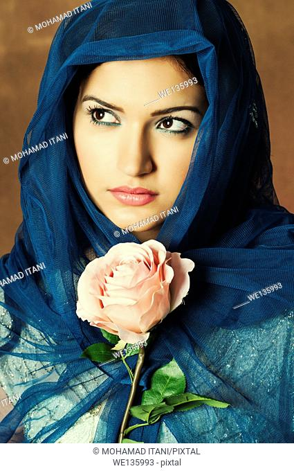 Veiled young woman with a pink rose