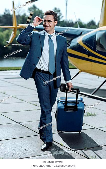 Experienced in travelling. Pleasant special agent carrying suitcase after a helicopter flight and waiting for a car to pick him up