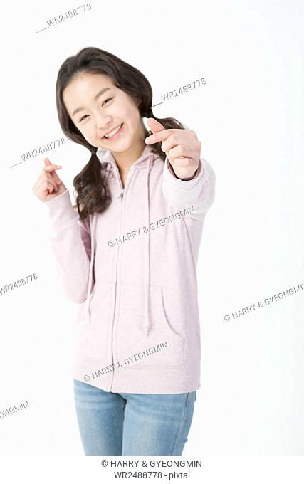 Smiling school girl making finger hearts