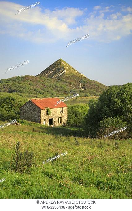 Great Treverbyn China Clay Tip near St Austell in Cornwall with a disused barn providing foreground interest. The image was captured on an evening in late May