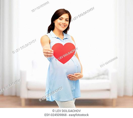 pregnancy, love, people and expectation concept - happy pregnant woman with red heart shape touching her belly over home room background