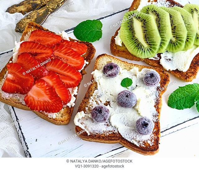 three square pieces of bread from white wheat smeared with curd top are fresh fruit, top view