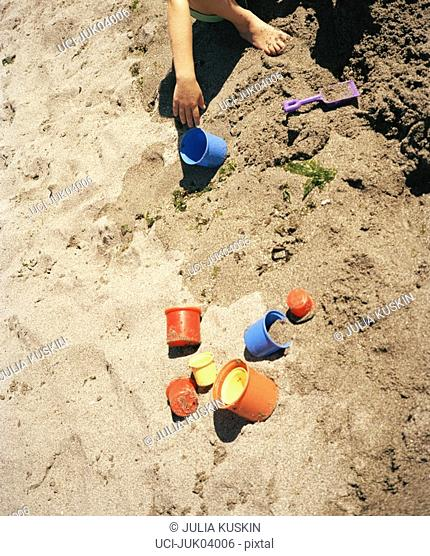 Young child playing in sand with toys