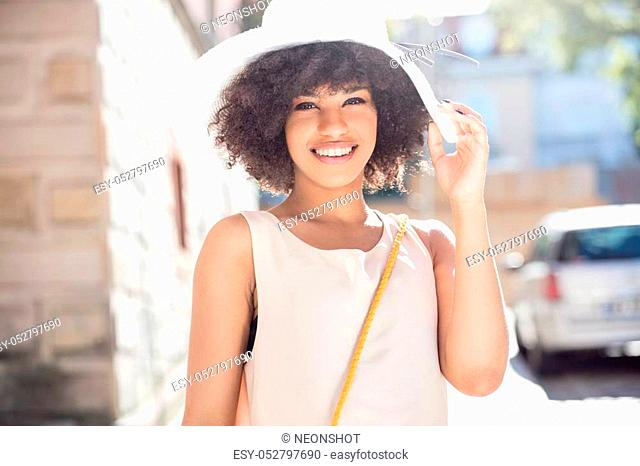 Summer in the city. Beautiful african american woman with afro hairstyle walking on the street