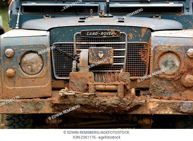 Close up of the front end of a Land Rover with mud on its grill