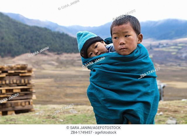 A Bhutanese boy carrying his little brother on his back, Phobjikha Valley, Gangtey, Bhutan, Asia