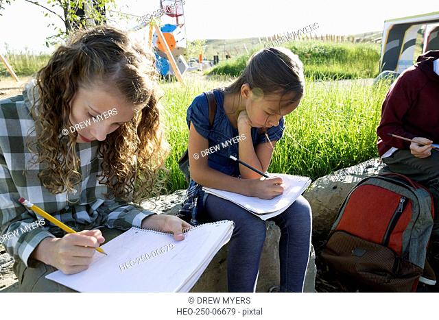 Students doing homework at sunny playground