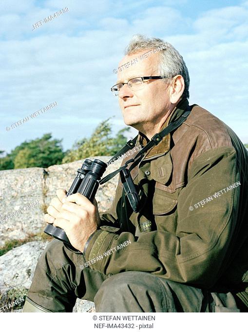 Man sitting with his binoculars ready, Sweden