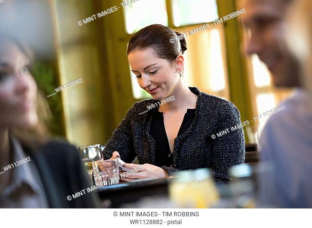 Business people outdoors, keeping in touch while on the go. Three people around a cafe table, one of whom is checking their phone