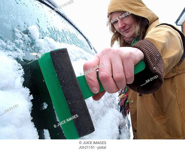 Woman scraping ice off car window