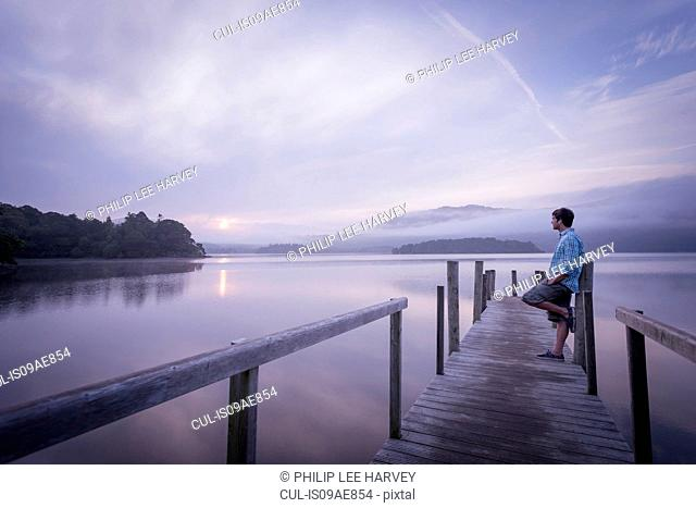 Man on pier by tranquil lake, Cumbria, England, UK
