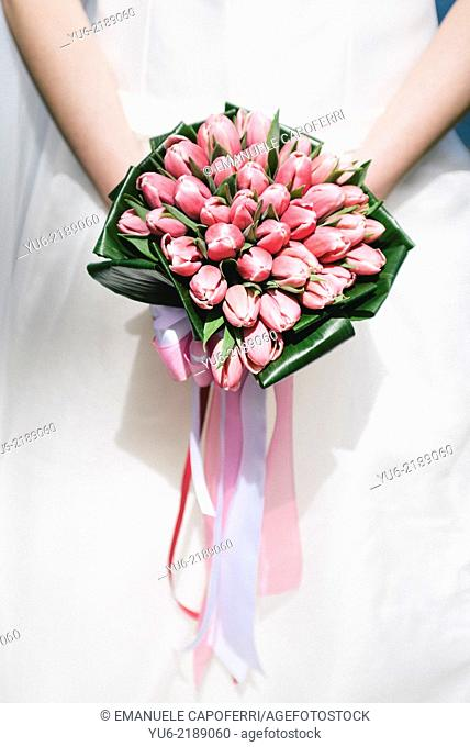 Hands of the bride with a bouquet of tulips