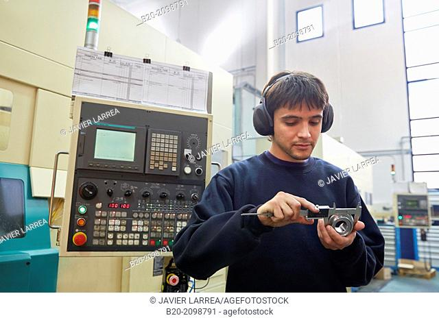 Worker measuring with caliper. Area automated CNC lathes. Machined Indecober. Machining of precision parts in series. Automotive industry. Berriz