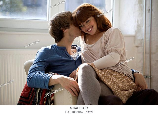 A young man kissing his girlfriend who's sitting on his lap