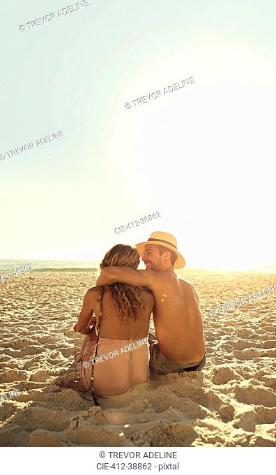 Affectionate young couple hugging on sunny summer beach