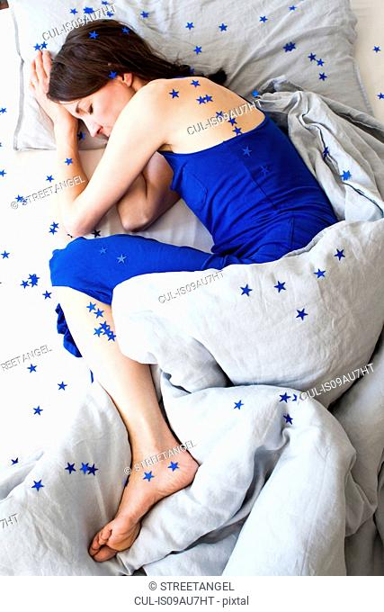 Overhead view of mature woman wearing blue pyjamas lying curled up in bed covered in stars