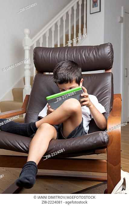 Boy plays on a tablet at home