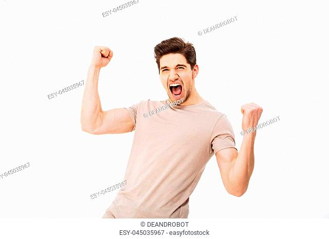 Photo of happy brunette guy rejoicing and clenching fists like winner or lucky person, isolated over white background
