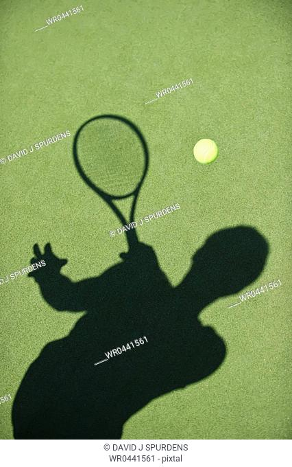 A tennis player sillhouette retuns the ball