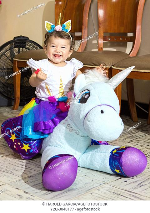Little baby riding a unicorn in a party with beautiful decoration