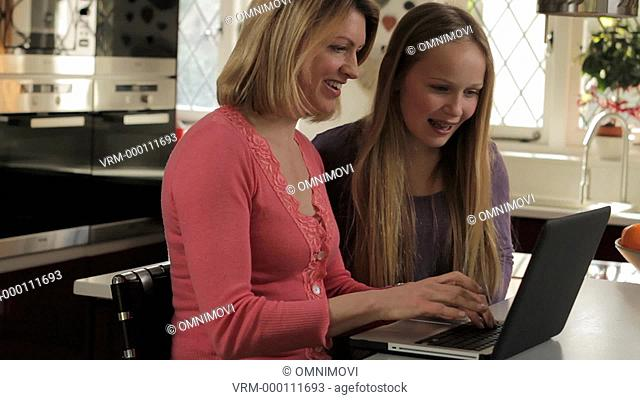 Mother and Daughter Entering Credit Card Details Online