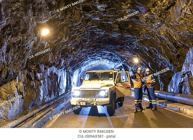 Workers with utility vehicle in tunnel of hydroelectric power station