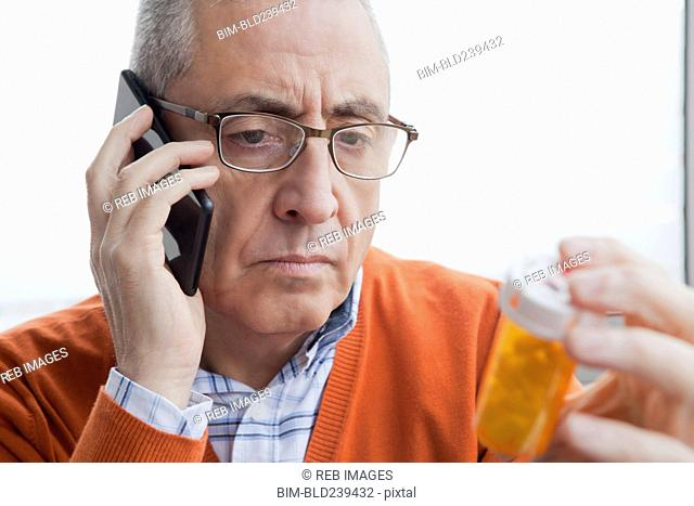 Serious Hispanic man talking on cell phone holding prescription bottle