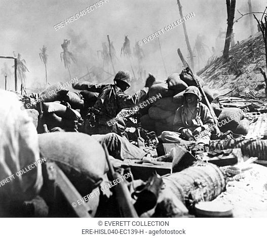Marine about to throw a hand grenade at a Japanese pillbox on Tarawa, Nov. 23, 1944. Smoke of the battle rolls over a hastily thrown up sandbag entrenchment...