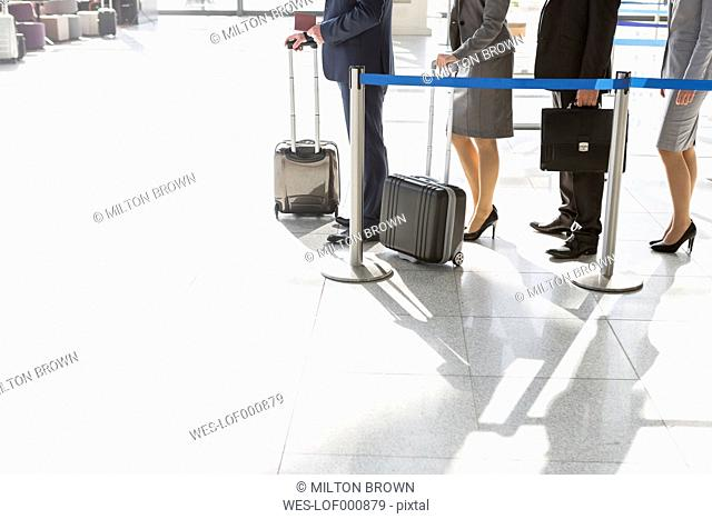Low section of businesspeople waiting in queue at airport check-in