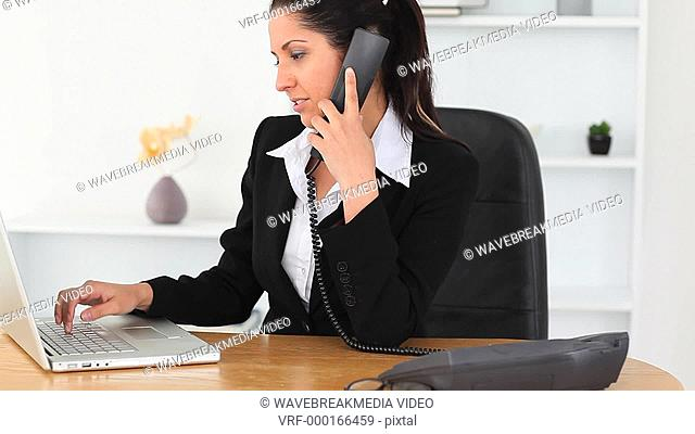 Smiling Businesswoman on the phone with a laptop in an office