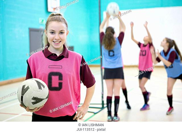 Portrait smiling high school student holding netball in gym class