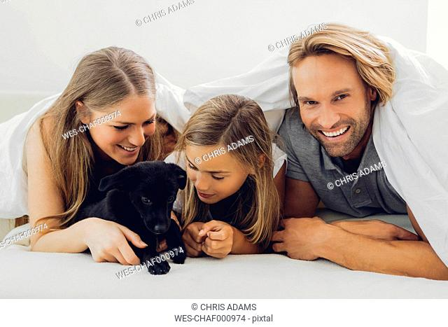 Happy father, mother and daughter with puppy in bed