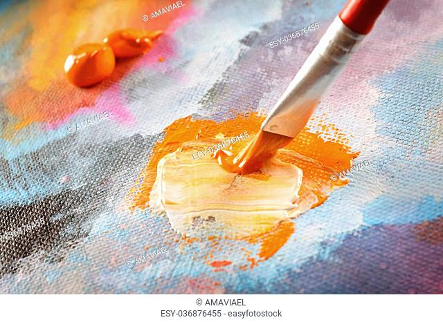 Artist hand with brush in acrylics paints on canvas