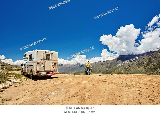 Peru, Chivay, Colca Canyon, woman with sons next to camper looking at canyon