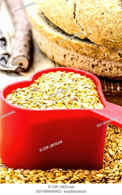Golden flax seeds with bread and heart closeup