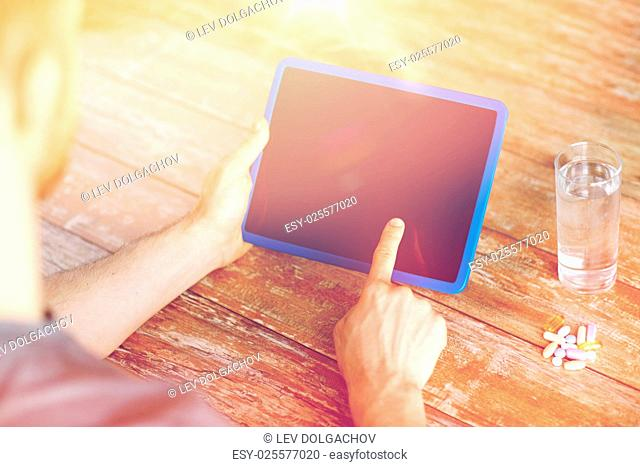 medicine, technology, nutritional supplements and people concept - close up of male hands pointing finger to blank tablet pc computer screen