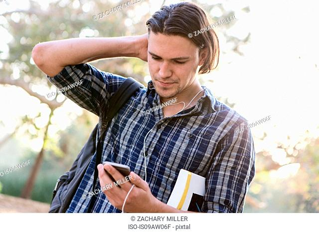 Angled view of young man, hand to head, looking down at smartphone